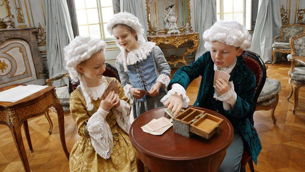 Children are playing cards in the Kinderreich; photo: Staatliche Schlösser und Gärten Baden-Württemberg, Michael Fuchs